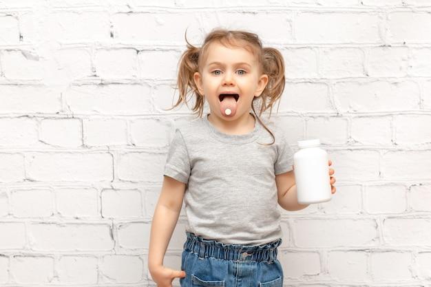 Bambino sorpreso con la pillola sulla sua lingua e che tiene le pillole bianche della medicina della bottiglia