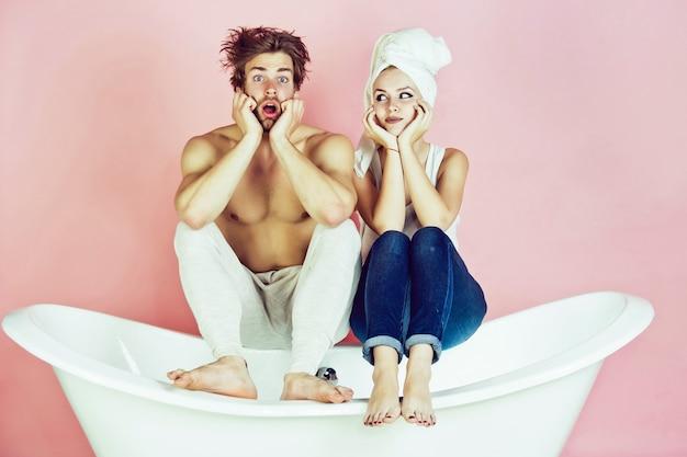 Coppia sorpresa di uomo e donna sulla vasca da bagno spa e bellezza relax e igiene sanitaria