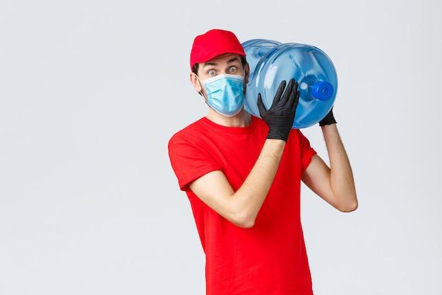 Corriere sorpreso in berretto rosso uniforme, guanti e maschera, fissando scioccato mentre porta l'acqua in bottiglia in ufficio o a casa