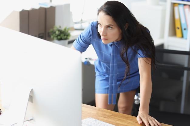 Donna scontenta sorpresa che guarda il monitor del computer sui problemi di lavoro sul posto di lavoro e male