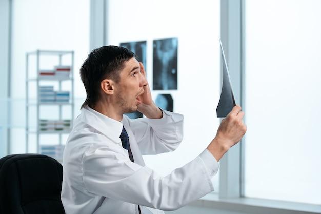 Medico sorpreso che esamina i raggi x del paziente