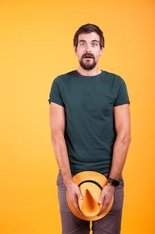 Uomo vestito sorpreso che copre le sue parti con un cappello su sfondo arancione