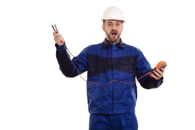 Ingegnere elettricista sorpreso in casco e uniforme con strumento tester