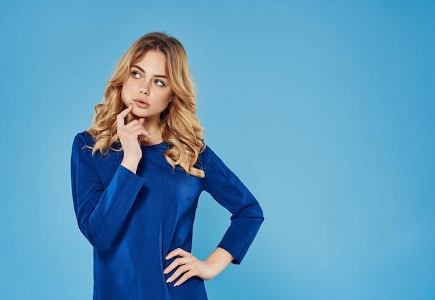Donna emotiva sorpresa in abito blu che gesticola con sfondo blu a mano
