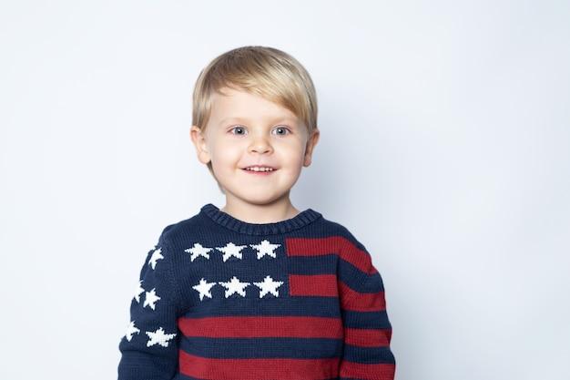 Bambino sorpreso ed entusiasta in un maglione con una bandiera americana su sfondo bianco.