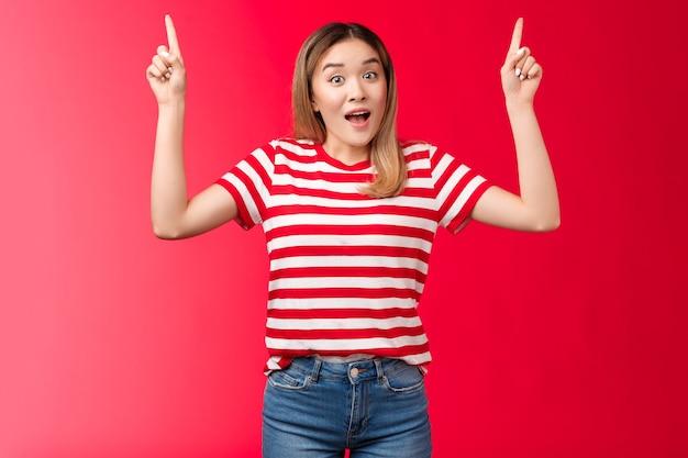 Sorpresa eccitata ragazza bionda asiatica carina che punta le dita indice alzate in alto, la ragazza che racconta un fantastico promo parla della pubblicità in alto entusiasta bocca aperta impressionata alza le sopracciglia curiosamente