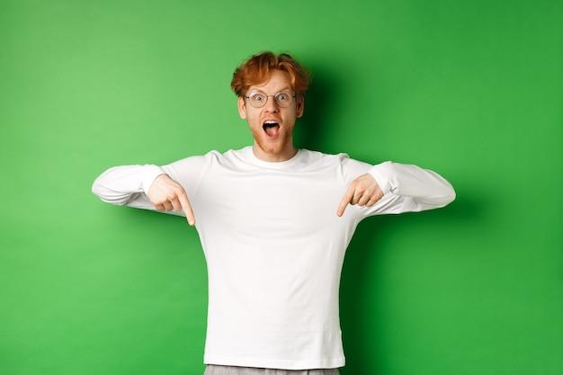 Giovane uomo dai capelli rossi sorpreso ed eccitato urla di gioia e stupore, guardando il fantastico promo, puntando il dito verso il basso, in piedi su sfondo verde.