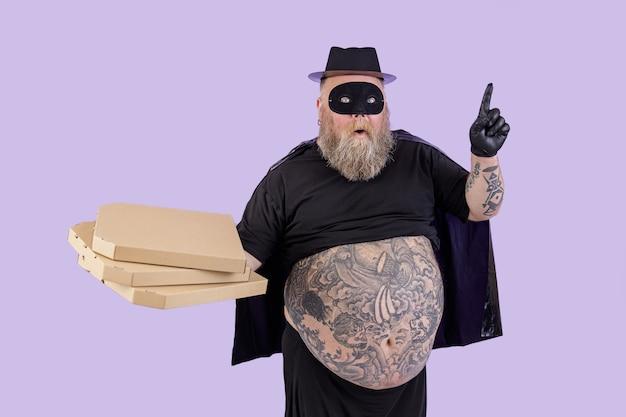 L'uomo grasso sorpreso in costume da zorro tiene le pizze e punta su sfondo viola