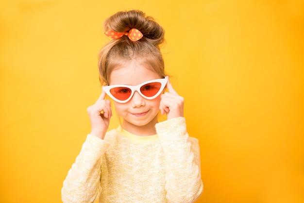 Bambina divertente sorpresa in occhiali da sole sulla parete gialla
