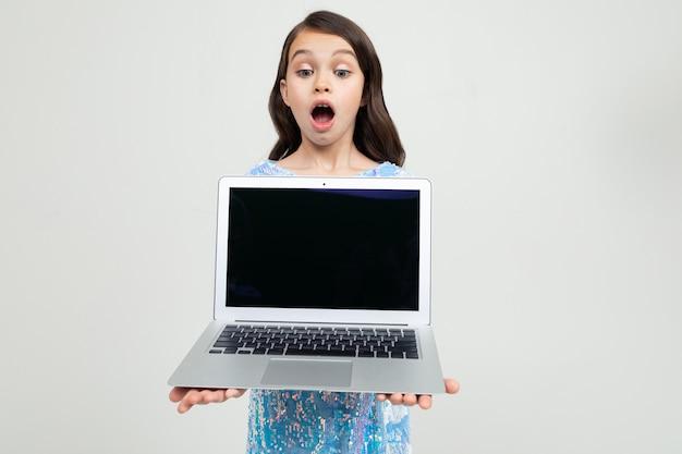 Ragazza sorpresa che tiene un computer portatile con un modello per l'inserimento di un sito web su una parete bianca