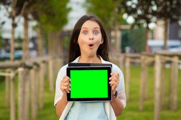 Una ragazza sorpresa tiene in mano un tablet finto all'aperto