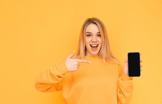 Ragazza sorpresa in abiti arancioni è su un giallo con uno smartphone in mano, mostra un dito su uno schermo bianco nero