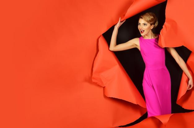 Ragazza sorpresa in abito rosa. donna sexy con trucco perfetto, labbra rosse che rompono lo sfondo della carta. copia spazio per pubblicizzare.