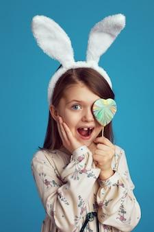 Ragazza sorpresa con orecchie da coniglio che copre l'occhio con un biscotto a forma di cuore