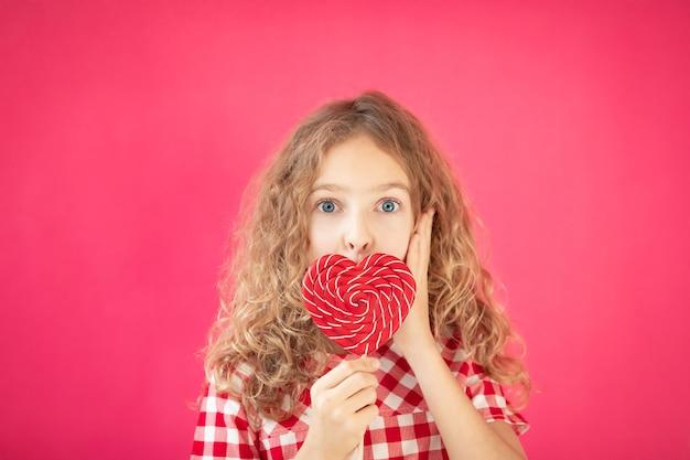Ragazza sorpresa con lecca-lecca a forma di cuore rosso su sfondo rosa concetto di san valentino