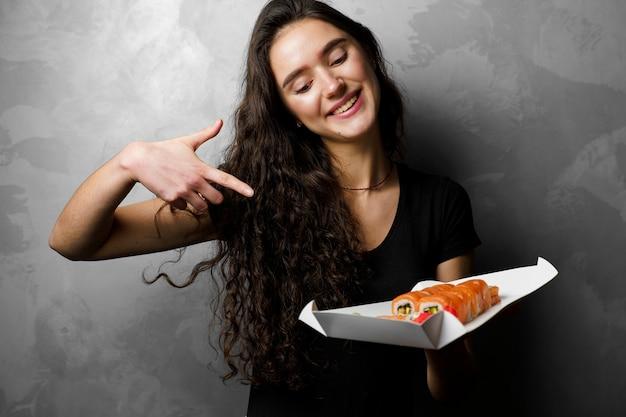 Ragazza sorpresa con sushi set philadelphia rotoli in una scatola di carta ragazza felice che tiene su uno sfondo grigio. consegna del cibo.
