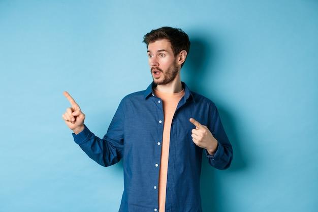 Ragazzo sorpreso in abiti casual, indicando e guardando a sinistra in uno spazio vuoto, mostrando pubblicità, in piedi su sfondo blu.