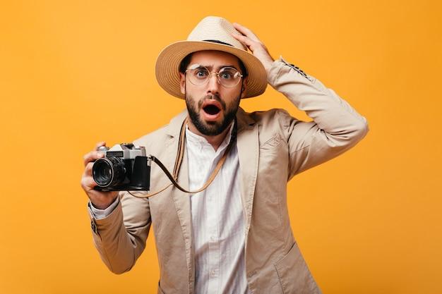 Ragazzo sorpreso in cappello e vestito beige che tiene macchina fotografica retrò