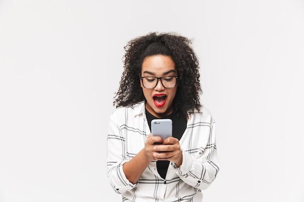Donna africana felice sorpresa in occhiali utilizza lo smartphone con la bocca aperta su sfondo grigio