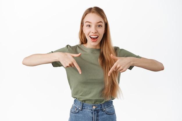 Ragazza carina felice sorpresa che punta le dita verso il basso, sembra stupita mentre mostra pubblicità, annuncio di un premio o collegamento a un evento, in piedi sul muro bianco in t-shirt