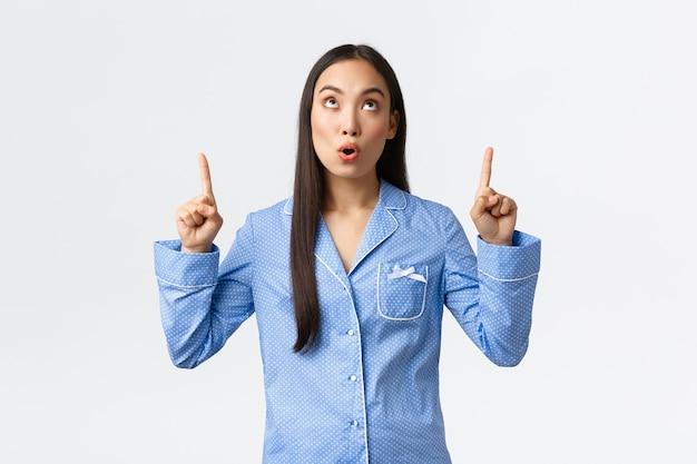 Ragazza asiatica sorpresa e colpita in jammies blu che guarda e punta le dita verso l'alto al banner promozionale. la donna in pigiama lascia a bocca aperta vedendo un annuncio pubblicitario impressionante