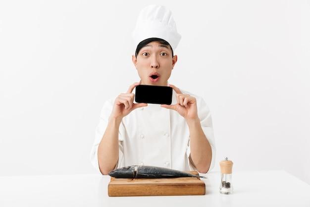 Sorpreso il capo giapponese in uniforme bianca del cuoco che tiene lo smartphone mentre filetto il pesce fresco crudo isolato sopra il muro bianco