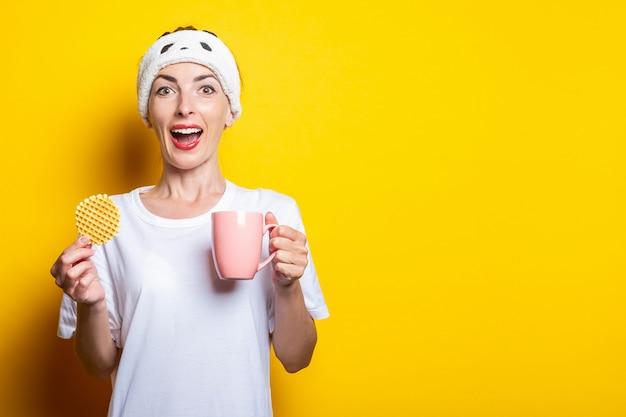 Giovane donna allegra sorpresa con una tazza di tè e waffle belga su sfondo giallo.