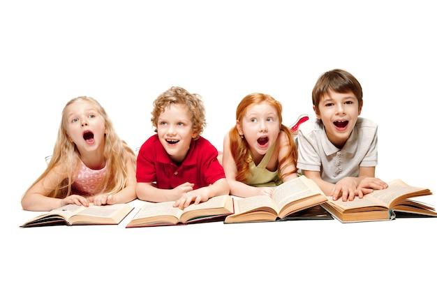 I bambini sorpresi ragazzo e ragazze posa con libri in studio, sorridendo, ridendo, isolato su bianco. giornata del libro, dell'istruzione, della scuola, del bambino, della conoscenza, dell'infanzia, dell'amicizia, del concetto di studio dei bambini