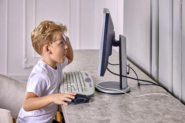 Il ragazzino sorpreso di 6 anni sta guardando il monitor del computer.