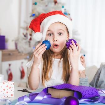 Bambina sorpresa in cappello della santa che tiene le palle blu e viola a natale