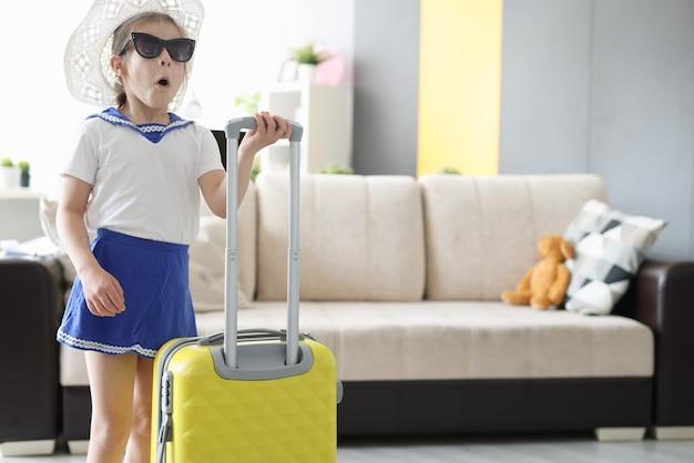 Bambina sorpresa in occhiali da sole e cappello in piedi con la valigia in mano a casa