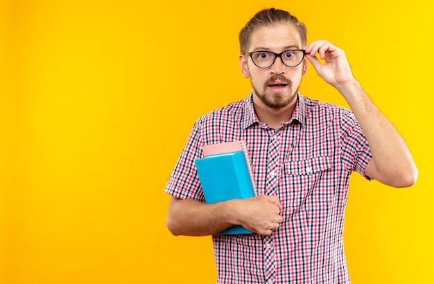 Sorpreso dall'aspetto fotocamera giovane studente che indossa uno zaino con gli occhiali che tengono un libro isolato sulla parete arancione con spazio di copia