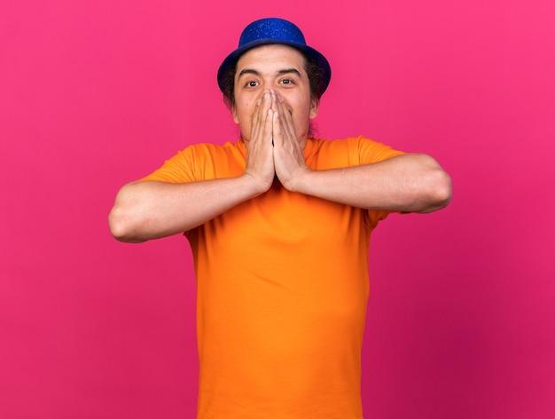 Sorpreso dall'aspetto fotocamera giovane uomo che indossa il cappello da festa volto coperto