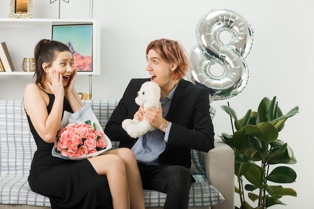 Sorpreso a guardarsi l'un l'altro giovane coppia in una felice giornata delle donne che tiene in mano un orsacchiotto con un bouquet seduto sul divano nel soggiorno