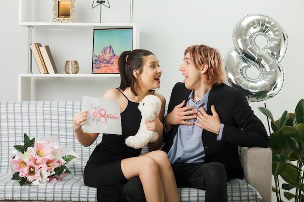 Sorpreso guardando l'un l'altro giovane coppia il giorno della donna felice con orsacchiotto e biglietto di auguri ragazzo mettendo le mani sul cuore seduto sul divano in soggiorno