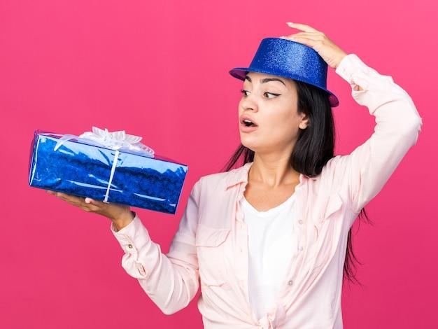Sorpreso lato giovane bella ragazza che indossa un cappello da festa con scatola regalo
