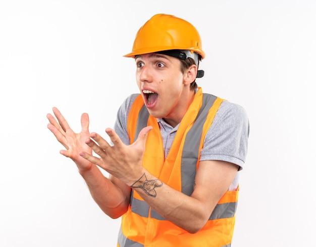 Sorpreso cercando lato giovane costruttore uomo in uniforme isolato su muro bianco
