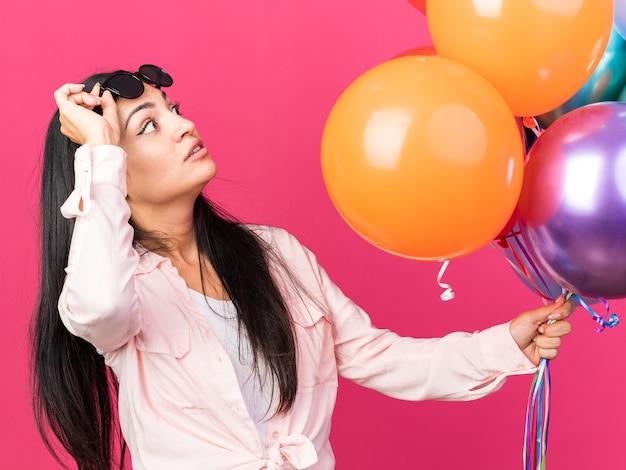 Sorpreso cercando giovane bella ragazza con gli occhiali che tengono palloncini