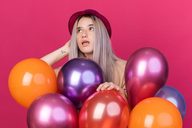 Sorpreso che cerca giovane bella ragazza che indossa un cappello da festa con bretelle dentali in piedi dietro palloncini isolati su una parete rosa