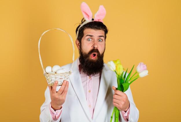 Uomo sorpreso in orecchie da coniglio con cesto di uova e fiori primaverili, vacanze di pasqua.