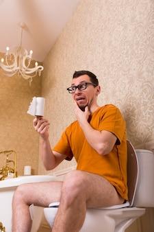 Uomo sorpreso con gli occhiali seduto sul water, senza carta