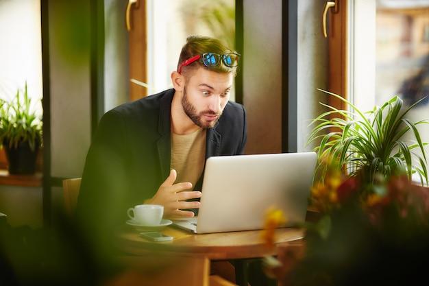 Uomo sorpreso al laptop
