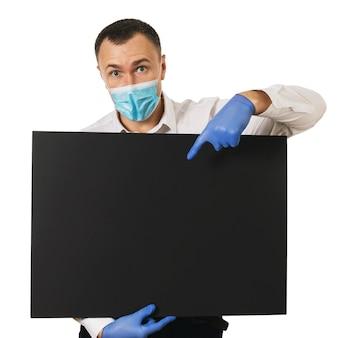 L'uomo sorpreso con una maschera medica e guanti mostra il dito indice fino al punto per il testo
