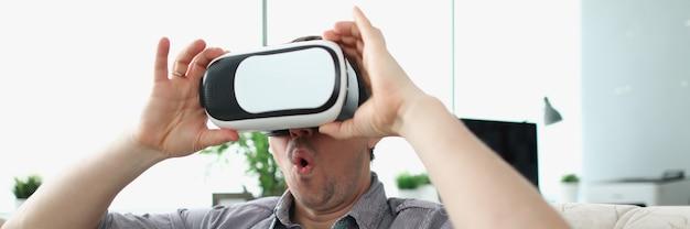 Uomo sorpreso che indossa occhiali per realtà virtuale seduto sul divano di casa
