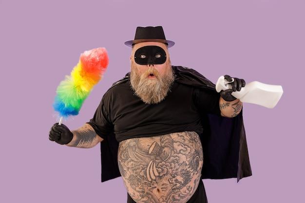 L'uomo sorpreso con sovrappeso in abito di carnevale tiene pennello e flacone spray su sfondo viola