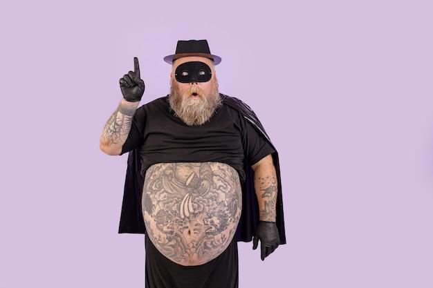 L'uomo sorpreso con sovrappeso in tuta da eroe ha avuto un'idea e punta su sfondo viola