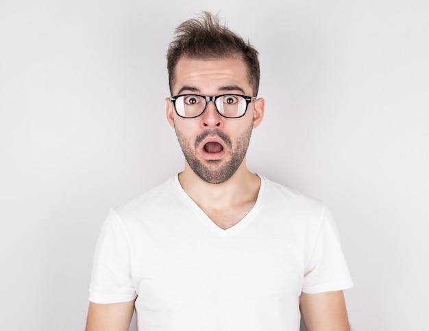 Uomo sorpreso con i capelli arruffati con gli occhiali in maglietta bianca sul muro grigio