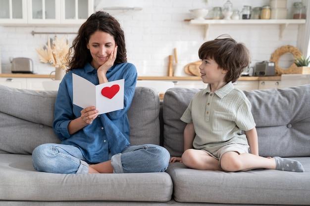 La madre sorpresa ha letto le congratulazioni dalla cartolina si siede vicino al figlio piccolo si congratula con il compleanno