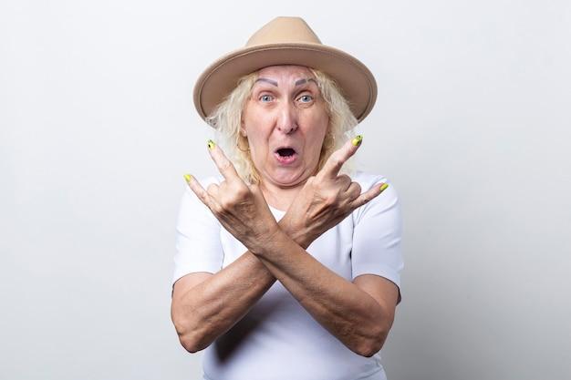 L'anziana sorpresa in cappello mostra il gesto del corno a bilanciere su sfondo chiaro.