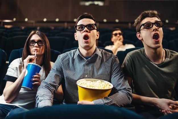 Persone sorprese in occhiali 3d con popcorn e bevande guardando film al cinema. industria dell'intrattenimento